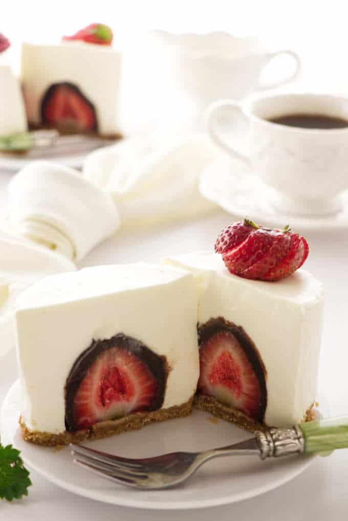 an individual cheesecake sliced open to reveal a chocolate covered strawberry. Coffee cup in the background.