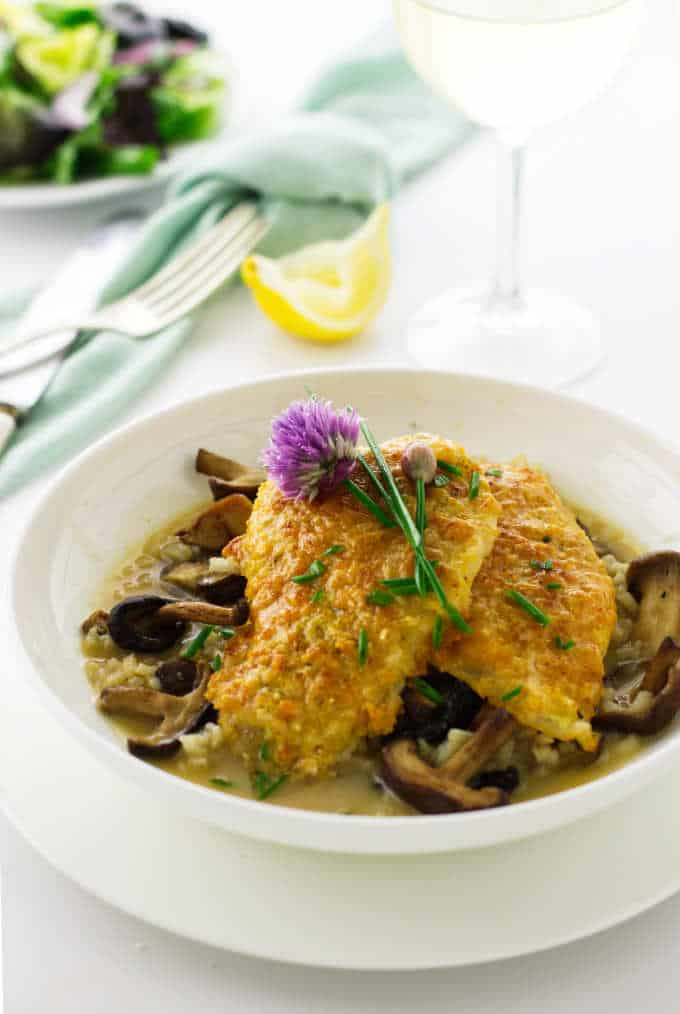 Serving bowl of creamy mushroom risotto, Parmesan crusted sole with chives and chive blossom