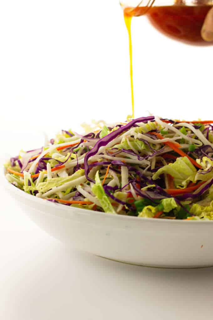 Bowl of kimchee slaw with a pour of kimchee vinaigrette