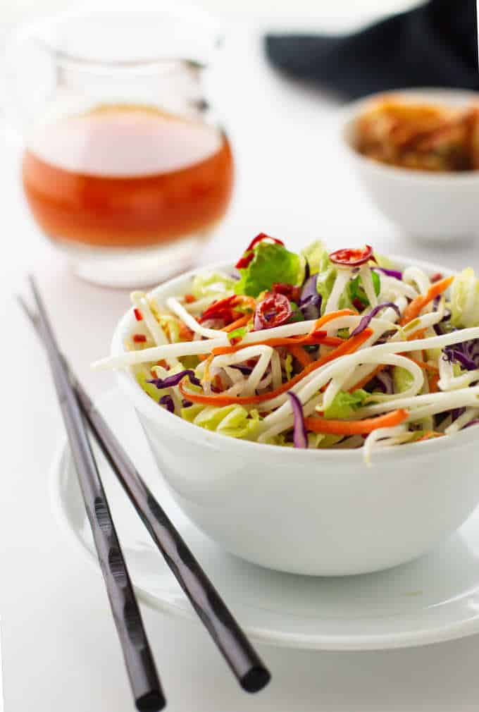 serving of kimchee slaw, dish of kimchi and pitcher of kimchee vinaigrette