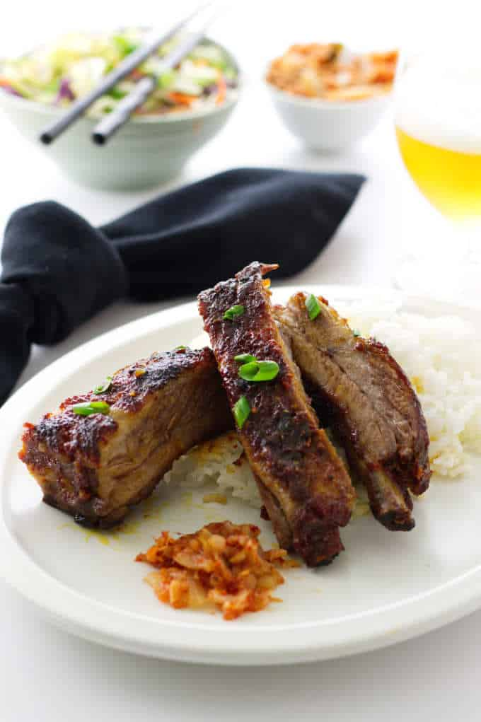 Serving of 3 Korean-style Pork Ribs, Rice, Kimchee..glass of beer and sides of kimchee slaw and kimchi