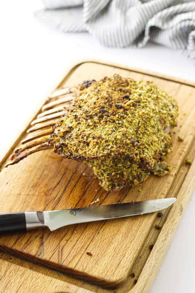 Roasted rack of lamb on cutting board with knife