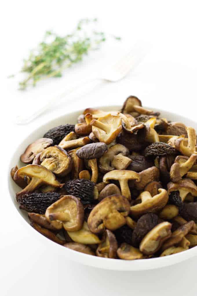 Bowl of sautéed mushrooms, fresh thyme and fork