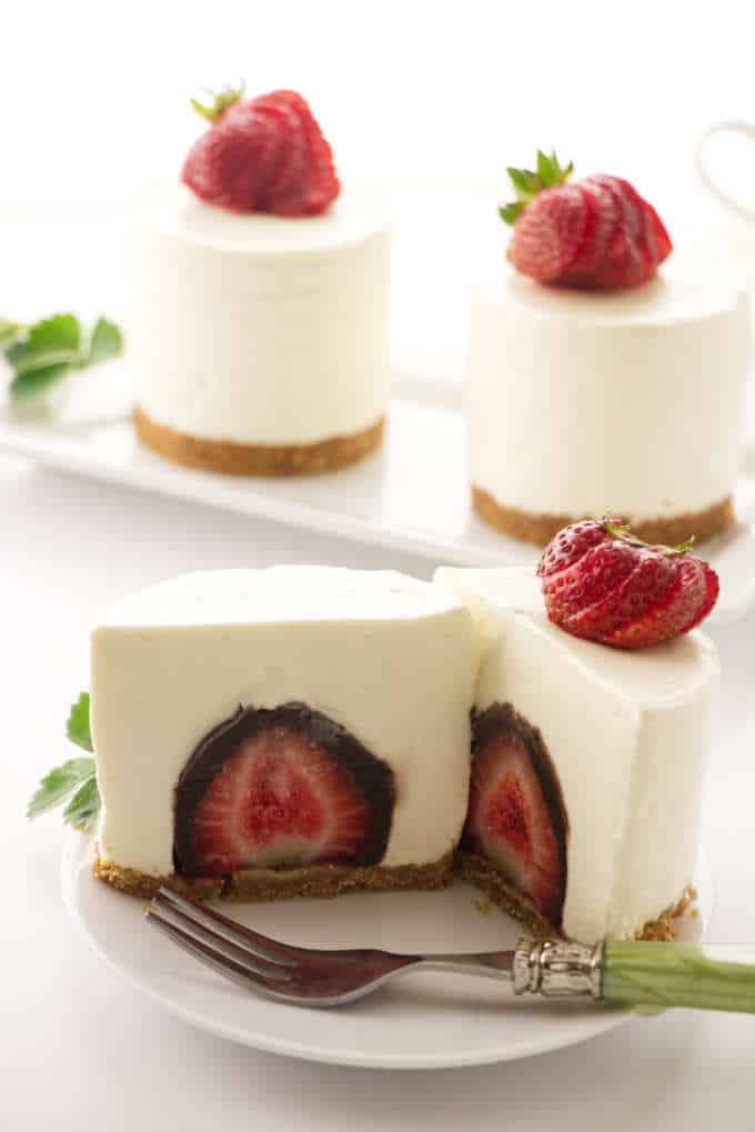 a no bake cheesecake sliced open to reveal a chocolate covered strawberry