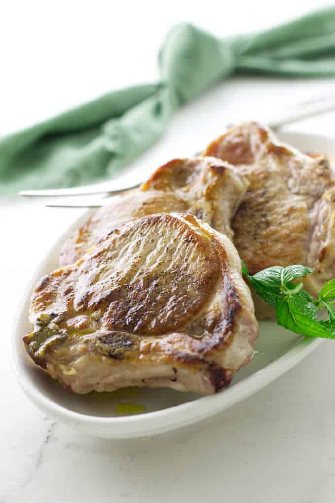 a serving dish with 4 oven roasted pork chops