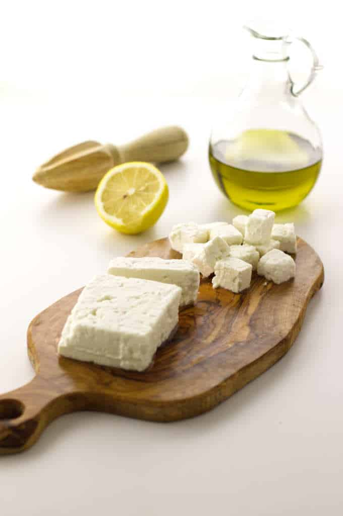 Cutting board with feta cheese, olive oil, lemon and lemon reamer