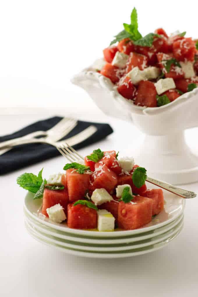 Serving of salad on stack of plates, bowl of salad, napkin/forks