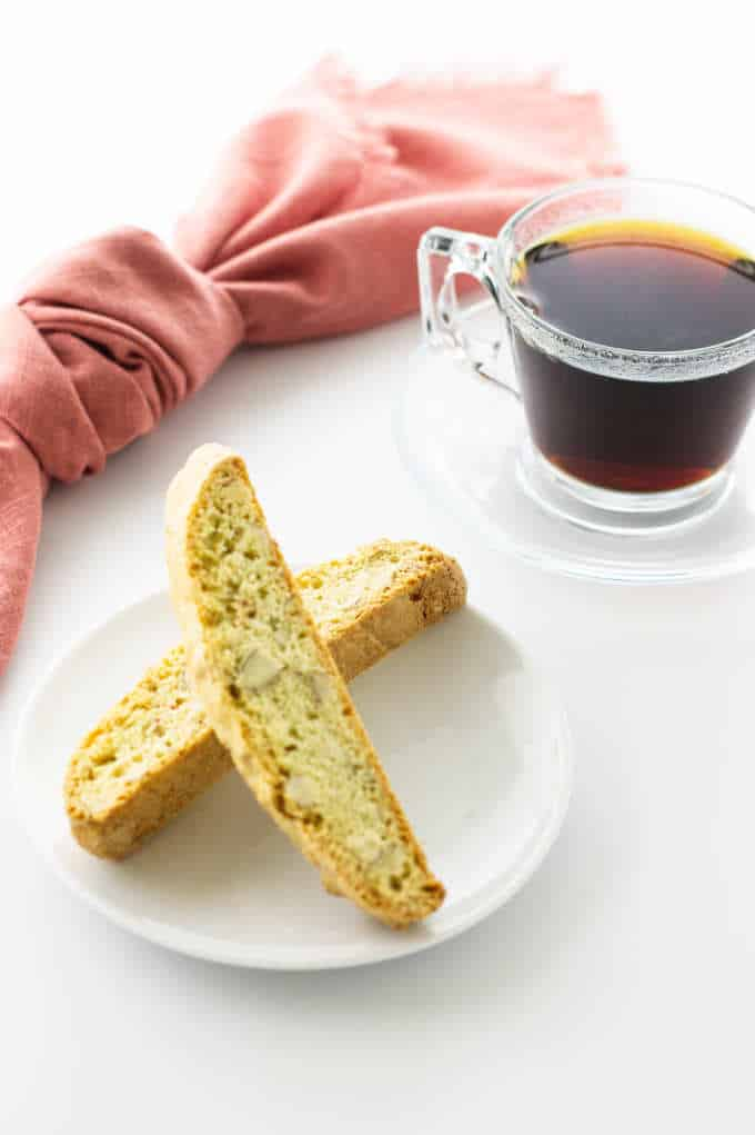 a plate of almond biscotti with a cup of coffee