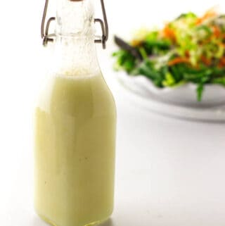 Bottle of preserved lemon vinaigrette and salad