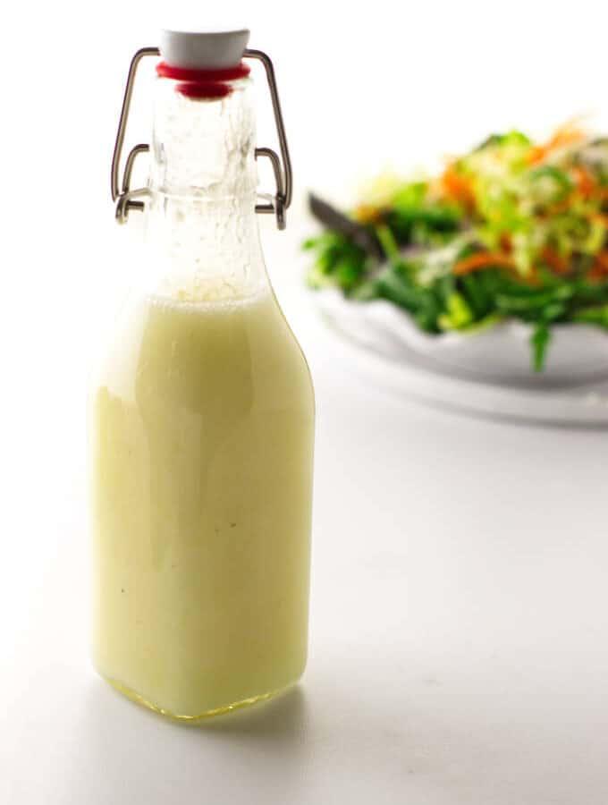 Bottle of preserved lemon vinaigrette and salad