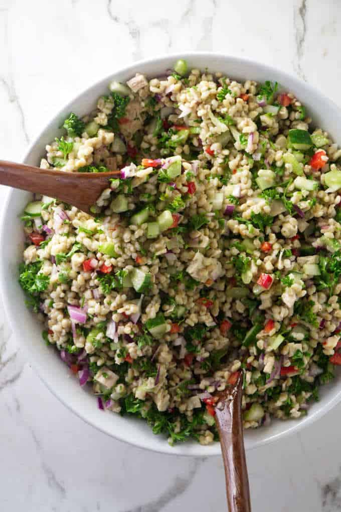 tossing the ingredients for chicken barley salad