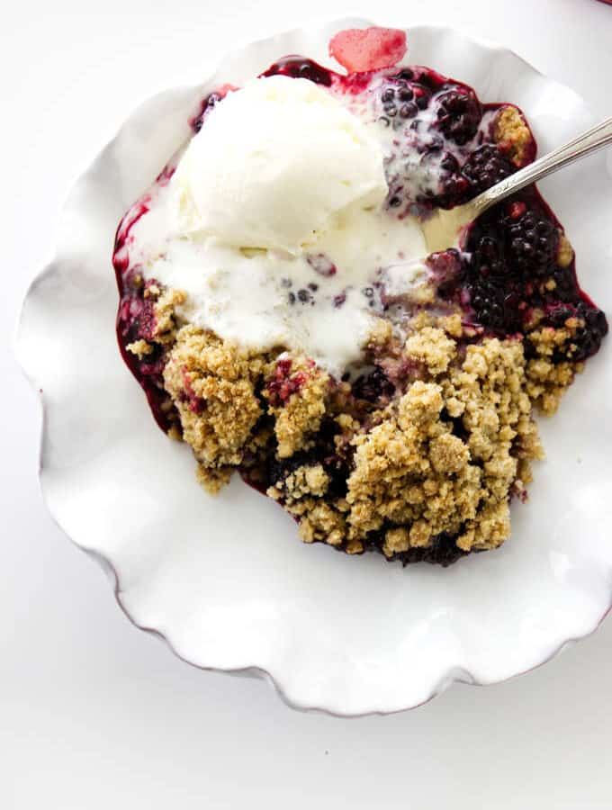 serving dish of blackberry crumble with vanilla ice cream