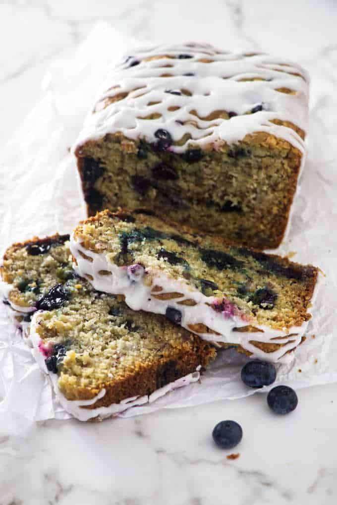 blueberry banana bread with two sliced in the foreground