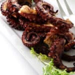 Overhead photo of grilled octopus legs on plate with serving fork