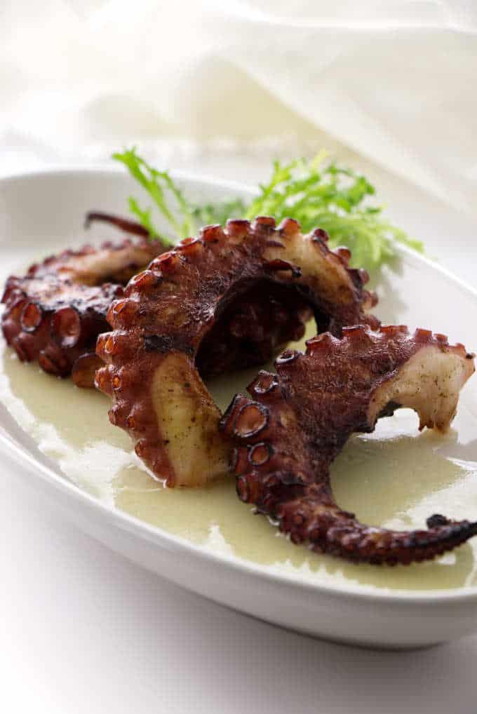 Three grilled octopus legs in pool of preserved lemon vinaigrette
