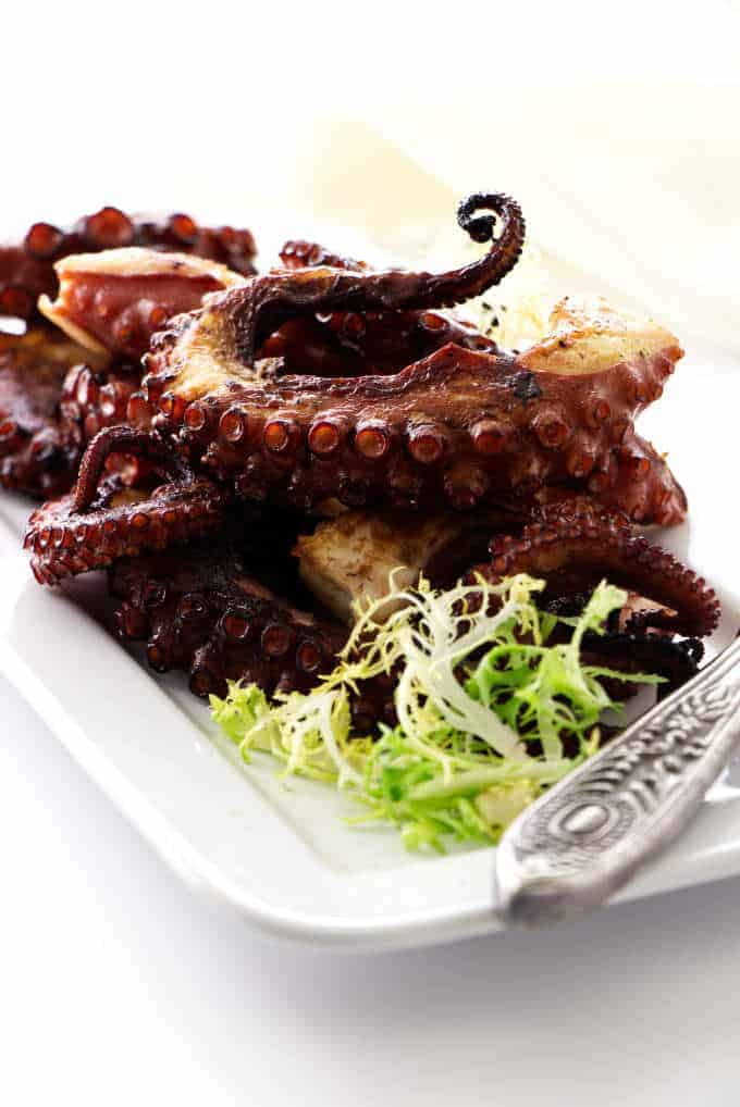 Grilled octopus legs on plate with greens