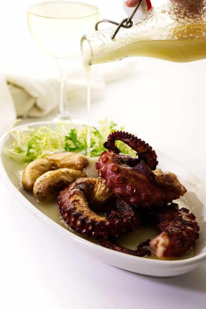 Serving of grilled octopus legs, potatoes and salad greens, lemon vinaigrette being poured over top