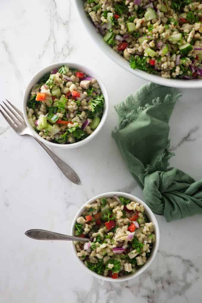 overhead shot of two small servings of barley salad next to a large serving bowl