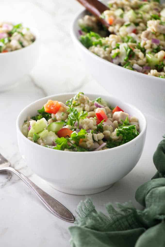 A small bowl of barley salad with a large serving dish in the background