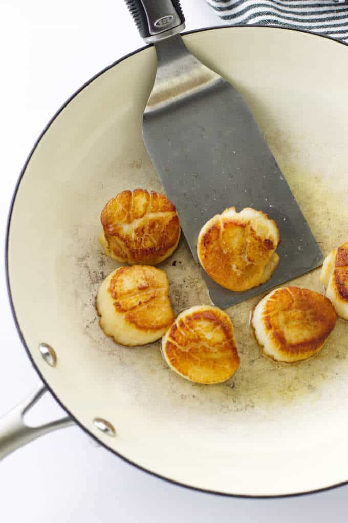 Six seared scallops in skillet with spatula
