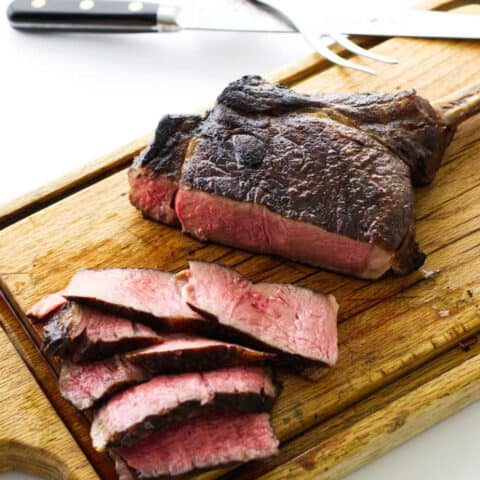 steak on cutting board with knife/fork