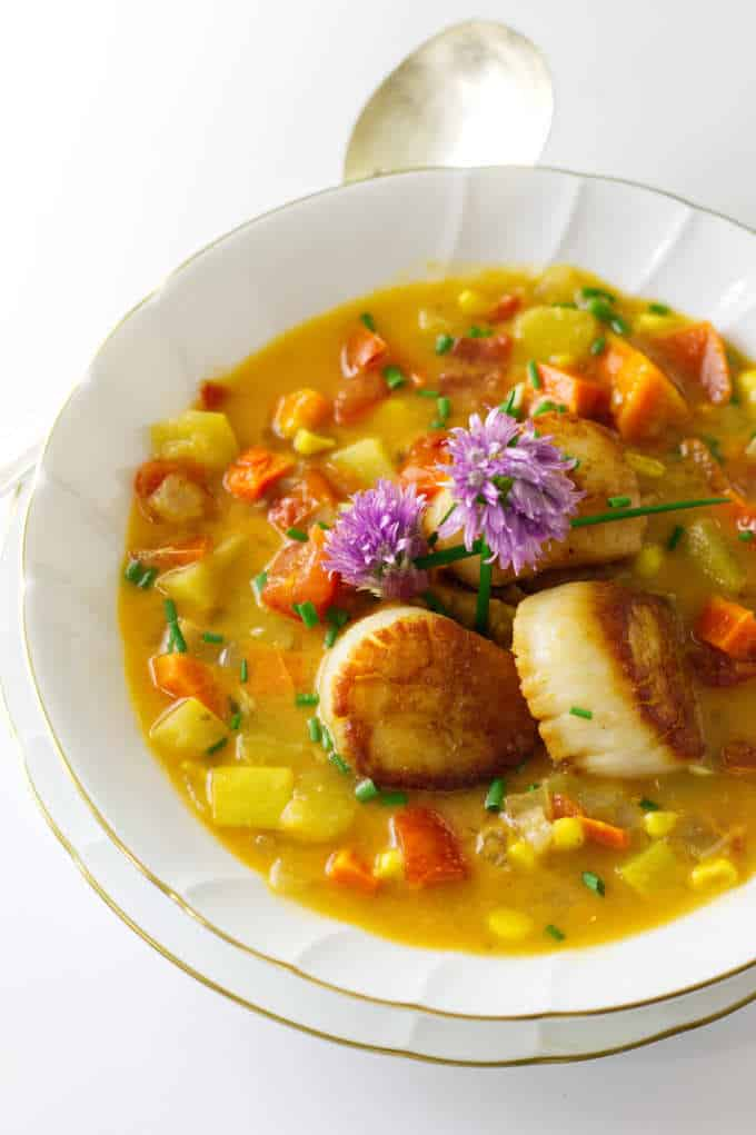 A bowl of vegetable chowder and three scallops, garnished with fresh chive blooms