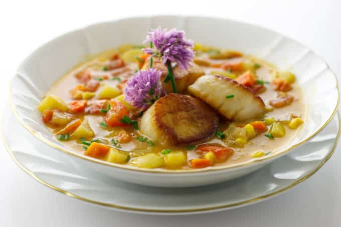 a bowl of vegetable chowder with 3 scallops and garnished with fresh chive blooms