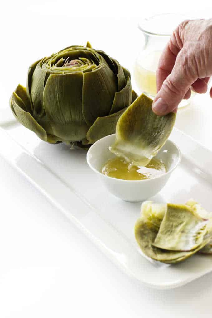 A steamed artichoke with dipping sauce
