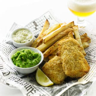 Oven fries, baked fish, mushy peas, tartar sauce and glass of beer