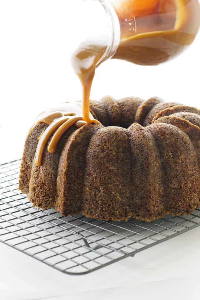 Apple Bundt Cake with Caramel Sauce being poured on.