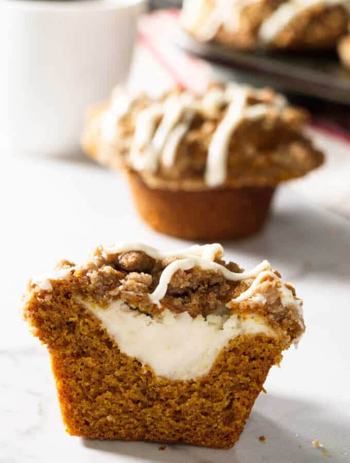 pumpkin muffin sliced open and showing cheesecake stuffing in the center