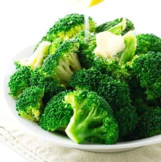 squeezing fresh lemon on steamed broccoli