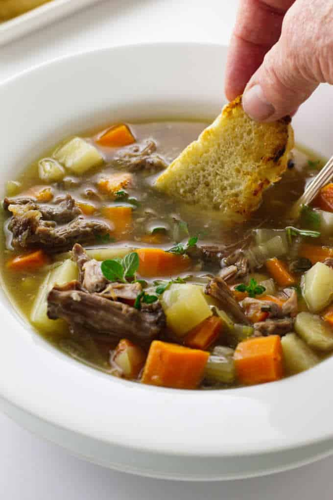 Oxtail soup with bread being dipped