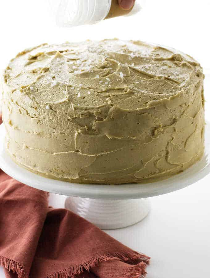 Cake on pedestal with salt being sprinkled on top