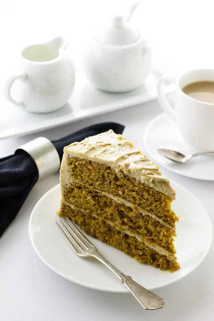 Pumpkin Spice Cake with Salted Caramel Frosting on a plate with fork, cup of coffee, napkin, cream and sugar