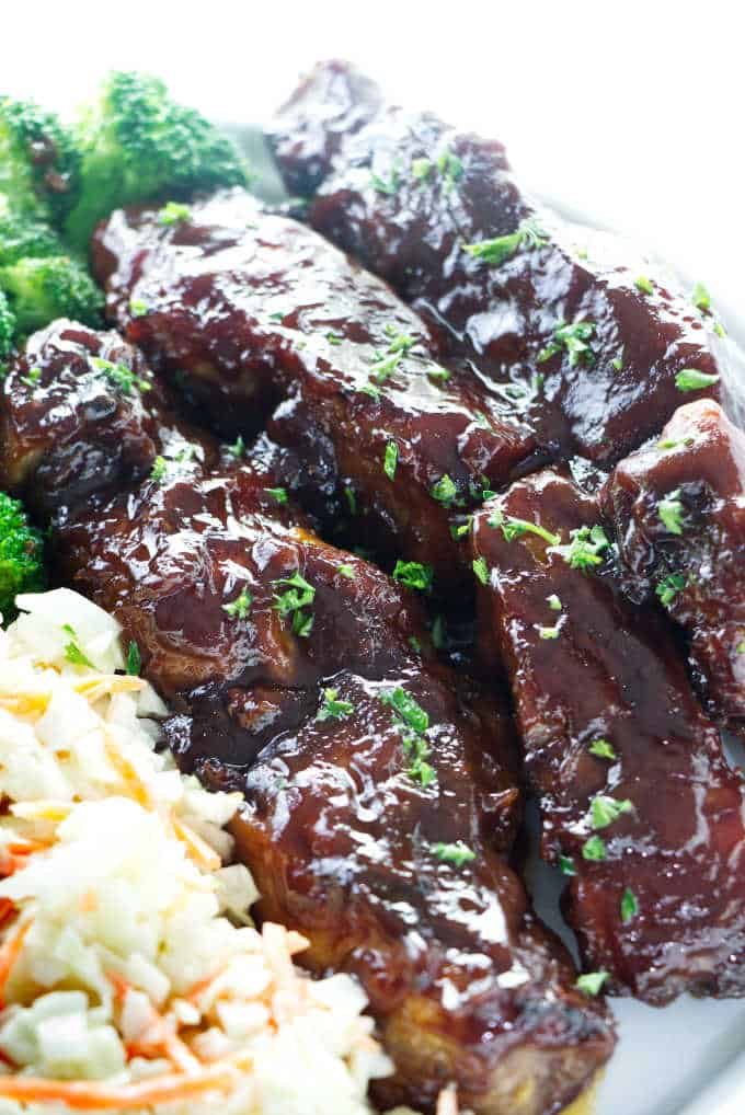 Three country style pork ribs on a plate with a salad and broccoli.