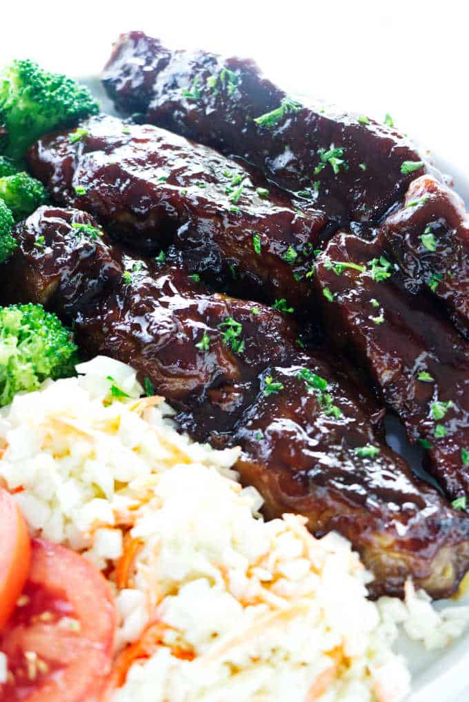 A plate of country style pork rib with coleslaw.