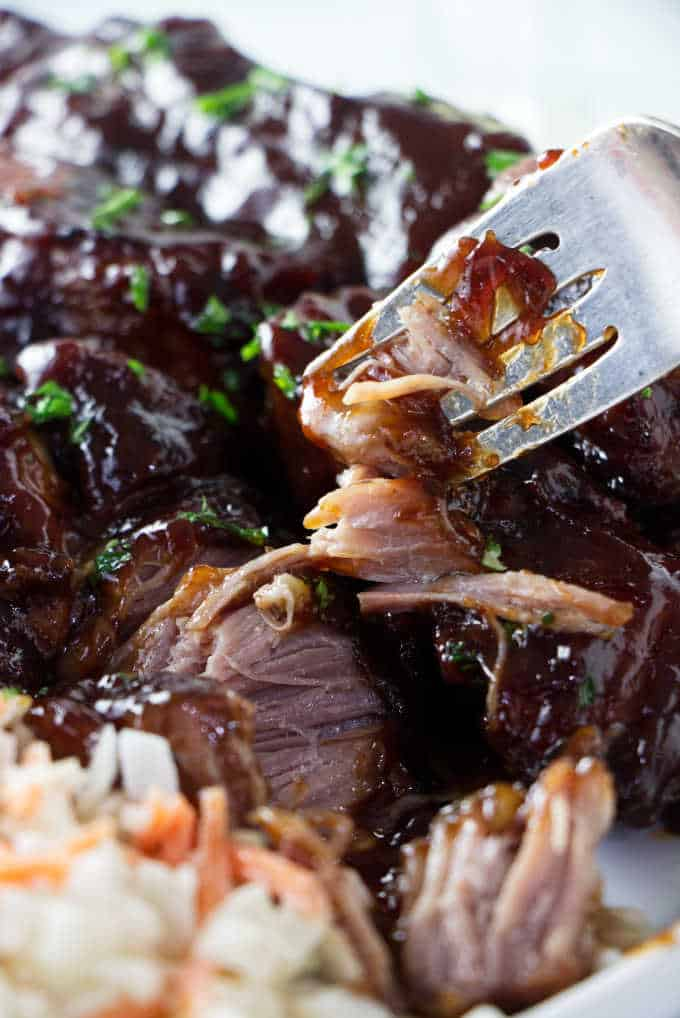 Close up of a country style pork rib being broken up with a fork.