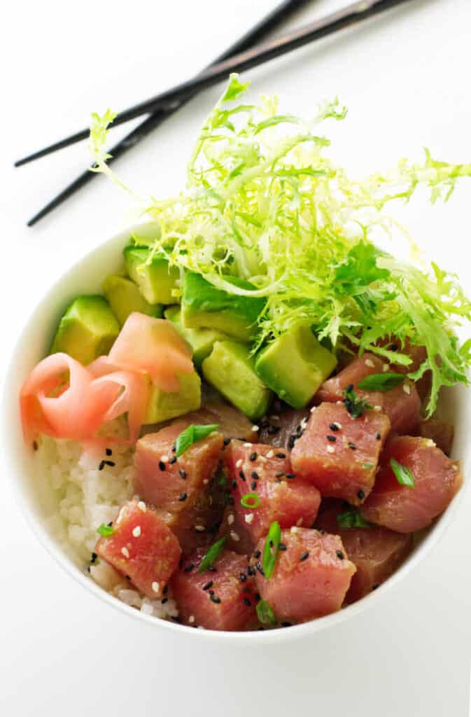 Tuna poke, avocado, sushi rice, salad greens in a bowl.