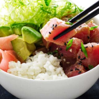 Bowl of tuna poké, chopsticks, avocado, rice and ginger