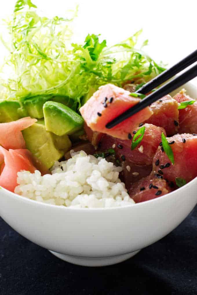 Bowl of tuna poké, chopsticks, avocado, rice and ginger