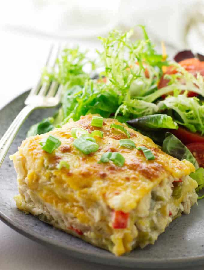 serving of chicken tortilla casserole on plate with salad and fork