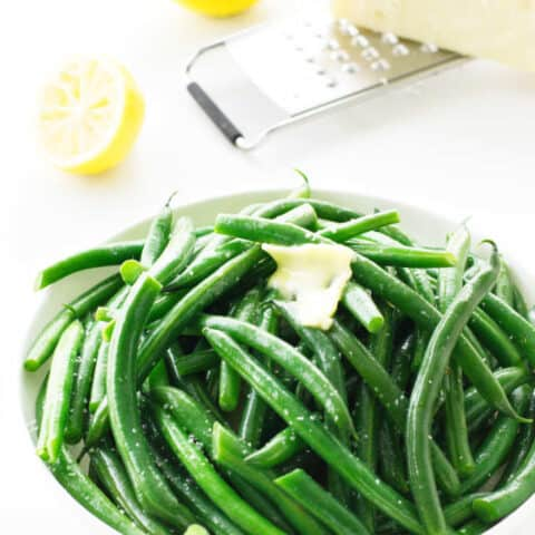 a bowl of steamed green beans with lemon, butter and parmesan cheese