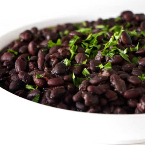 A serving dish with instant pot black beans and some parsley.