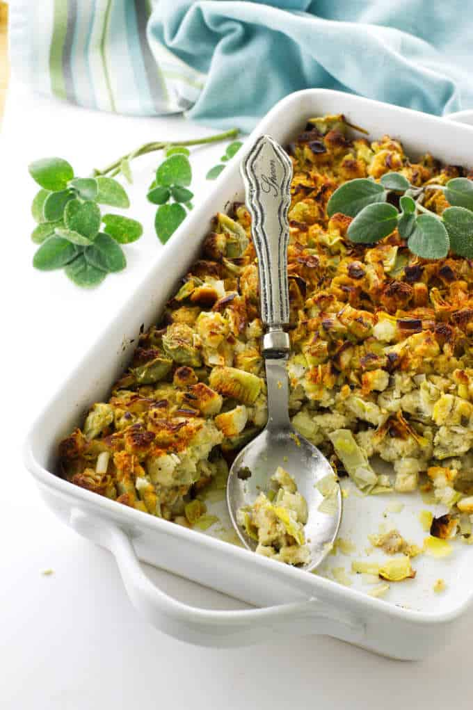 Dish of artichoke, fennel and leek stuffing with sage sprigs and serving spoon