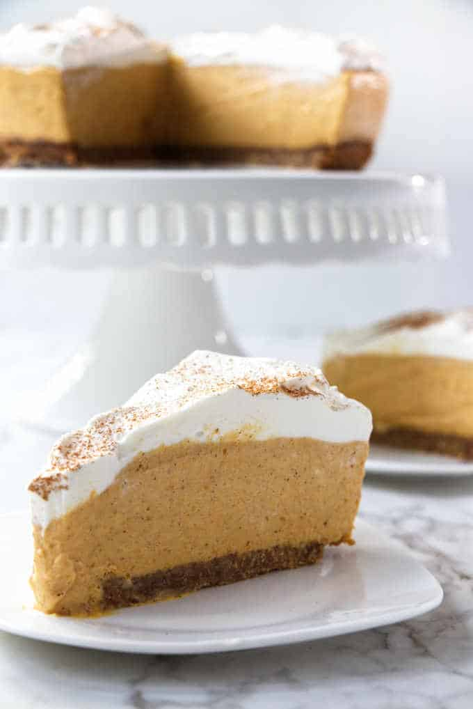 a slice of no-bake pumpkin cheesecake with a full cheesecake in the background