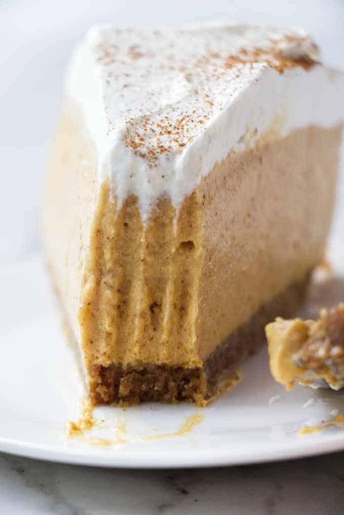A slice of no bake pumpkin cheesecake with a bite taken