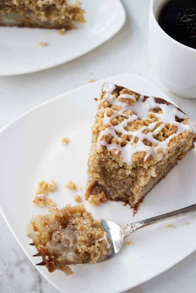 A slice of fresh pear cake with a fork and a cup of coffee.
