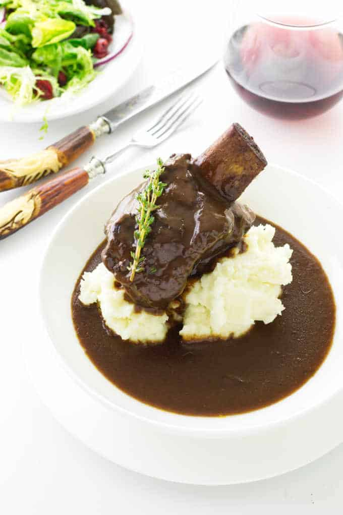 Dish with sauce, mashed potatoes, short ribs, wine and salad in background