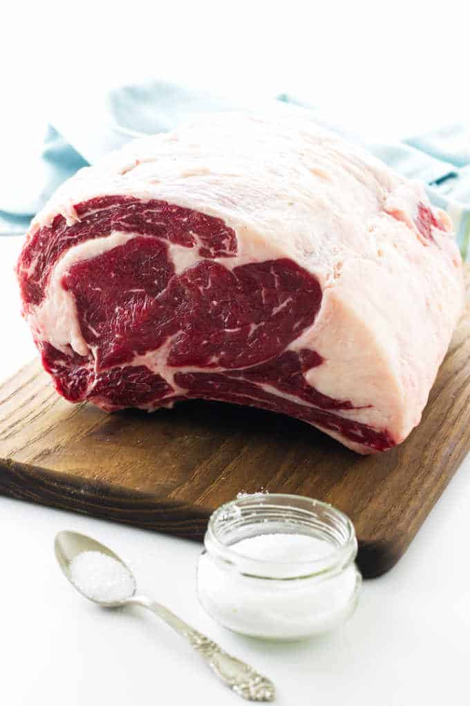 Uncooked rib roast on cutting board with salt and spoon